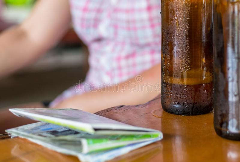 Δύο μπουκάλια της μπύρας σε ένα σκοτεινό καφετί μπουκάλι με έναν χάρτη τουριστών σε έναν ξύλινο πίνακα με το αντίγραφο χωρίζουν κ στοκ φωτογραφίες