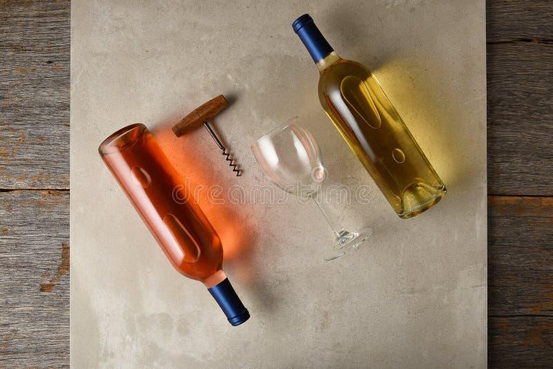 Δύο μπουκάλια του κρασιού σε μια γκρίζα επιφάνεια κεραμιδιών σε έναν αγροτικό ξύλινο πίνακα στοκ φωτογραφίες με δικαίωμα ελεύθερης χρήσης