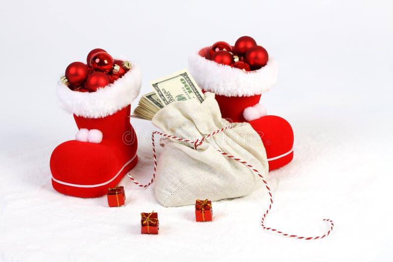 Δύο μπότες Santas με τις κόκκινες σφαίρες Χριστουγέννων χαλιών και η τσάντα Santas με το σωρό αμερικανικών λογαριασμών εκατό δολα στοκ εικόνες