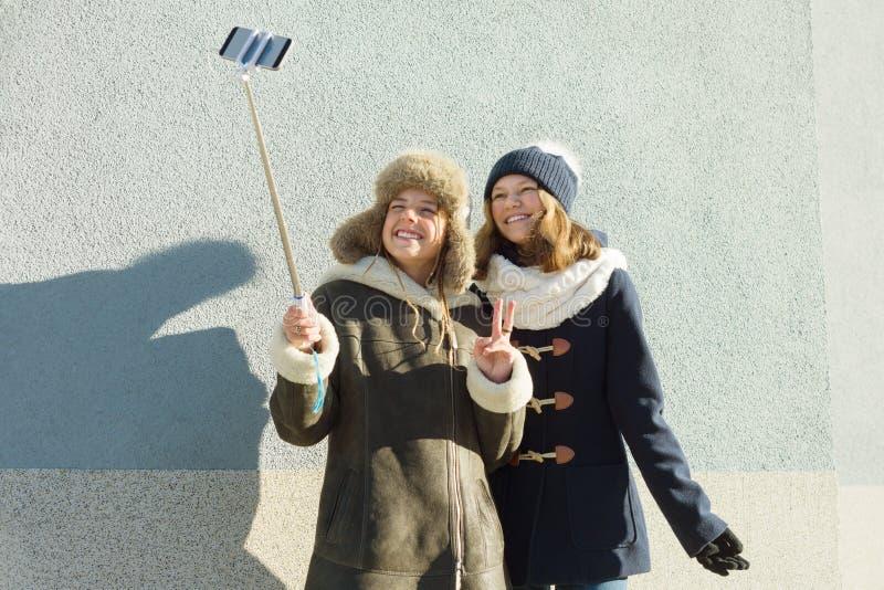 Δύο νέα έφηβη που έχουν τη διασκέδαση υπαίθρια, ευτυχείς χαμογελώντας φίλες στα χειμερινά ενδύματα που παίρνουν selfie, θετικοί ά στοκ φωτογραφία με δικαίωμα ελεύθερης χρήσης