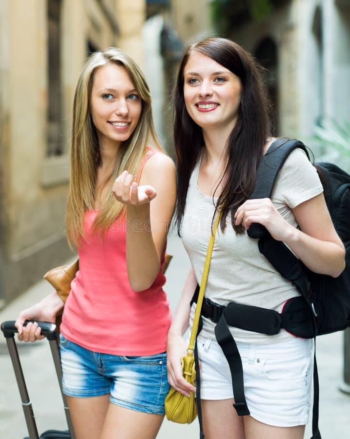 Δύο νέα κορίτσια με τις αποσκευές που ταξιδεύουν στις διακοπές στοκ φωτογραφία