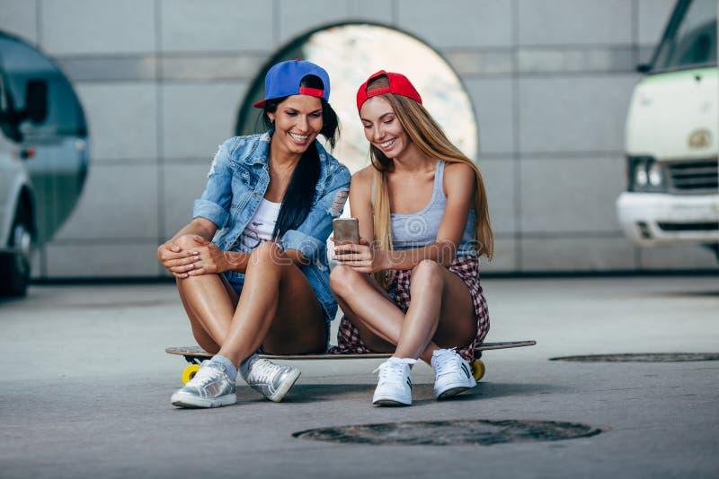 Δύο νέα κορίτσια που κάθονται στο longboard στοκ φωτογραφία με δικαίωμα ελεύθερης χρήσης