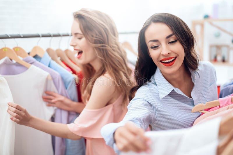 Δύο νέα κορίτσια στις αγορές Τα κορίτσια επιλέγουν τα ενδύματα στο κατάστημα Κορίτσια στην αίθουσα εκθέσεως στοκ φωτογραφία με δικαίωμα ελεύθερης χρήσης