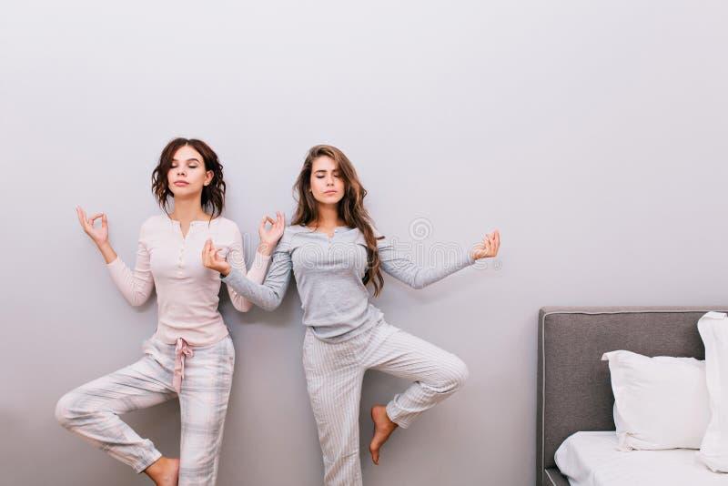 Δύο νέα όμορφα κορίτσια στις πυτζάμες νύχτας στο γκρίζο υπόβαθρο τοίχων Αυτοί που κάνουν την περισυλλογή με τις ιδιαίτερες προσοχ στοκ φωτογραφία
