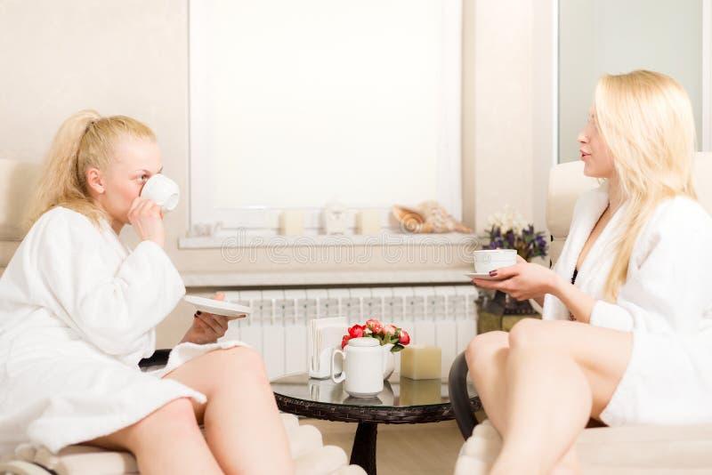 Δύο νέα όμορφα κορίτσια στο σαλόνι SPA οι ξανθές γυναίκες είναι χαριτωμένη ομιλία και τσάι και καφές κατανάλωσης στοκ φωτογραφία