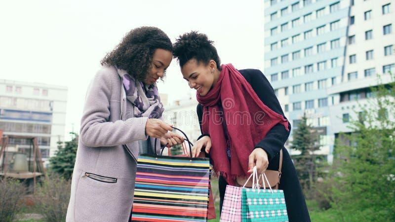 Δύο νέες γυναίκες αφροαμερικάνων που μοιράζονται τις νέες αγορές τους οι τσάντες ο ένας με τον άλλον Ελκυστική ομιλία κοριτσιών στοκ εικόνα