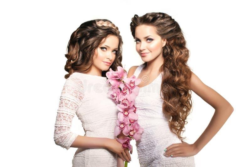 Δύο νέες γυναίκες ομορφιάς, μακριά σγουρή τρίχα πολυτέλειας με τη ορχιδέα flowe στοκ εικόνα με δικαίωμα ελεύθερης χρήσης