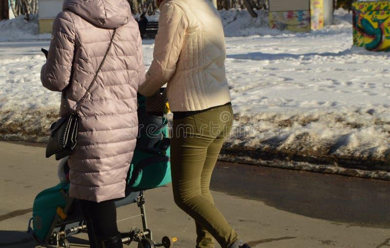 Δύο νέες γυναίκες περπατούν στο πάρκο με έναν περιπατητή μια ηλιόλουστη ημέρα άνοιξη στοκ εικόνες με δικαίωμα ελεύθερης χρήσης