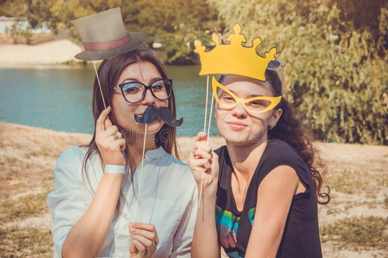 Δύο νέες γυναίκες που θέτουν χρησιμοποιώντας τα στηρίγματα θαλάμων φωτογραφιών στοκ φωτογραφία