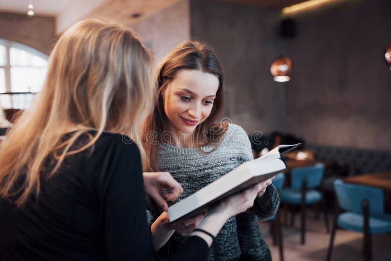 Δύο νέες γυναίκες που κάθονται στον καφέ κατανάλωσης καφέδων και απόλαυση στα καλά βιβλία Σπουδαστές στο διάλειμμα Εκπαίδευση στοκ εικόνες