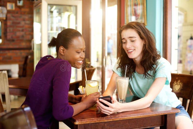 Δύο νέες γυναίκες που κάθονται στον καφέ με το κινητό τηλέφωνο στοκ φωτογραφία