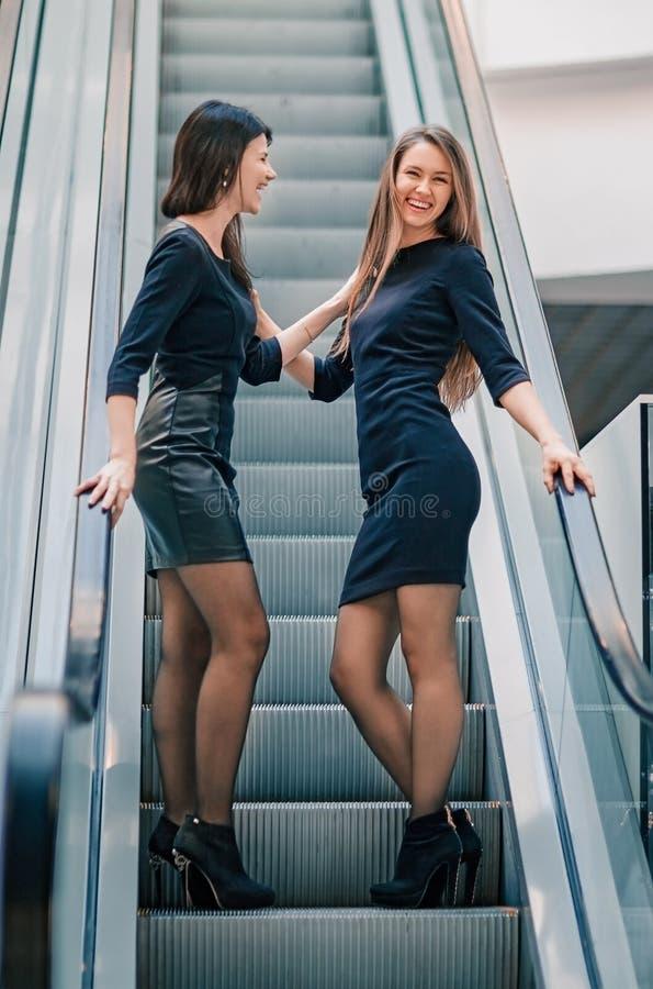 Δύο νέες γυναίκες που στέκονται στα βήματα της κυλιόμενης σκάλας στο εμπορικό κέντρο στοκ φωτογραφίες