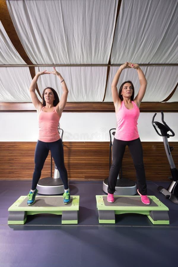 Δύο νέες γυναίκες που τεντώνουν stepper τη γυμναστική στοκ φωτογραφία