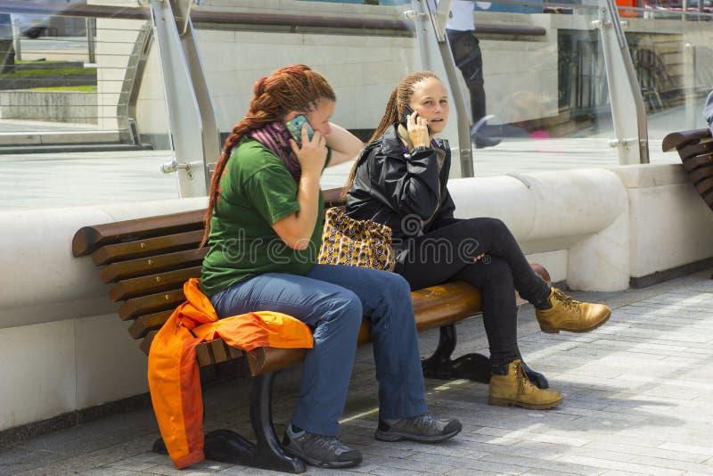 Δύο νέες γυναίκες που χρησιμοποιούν τα κινητά τηλέφωνά τους χαλαρώνοντας στην ακτή στον ποταμό Lagan του Μπέλφαστ ` s στοκ εικόνες