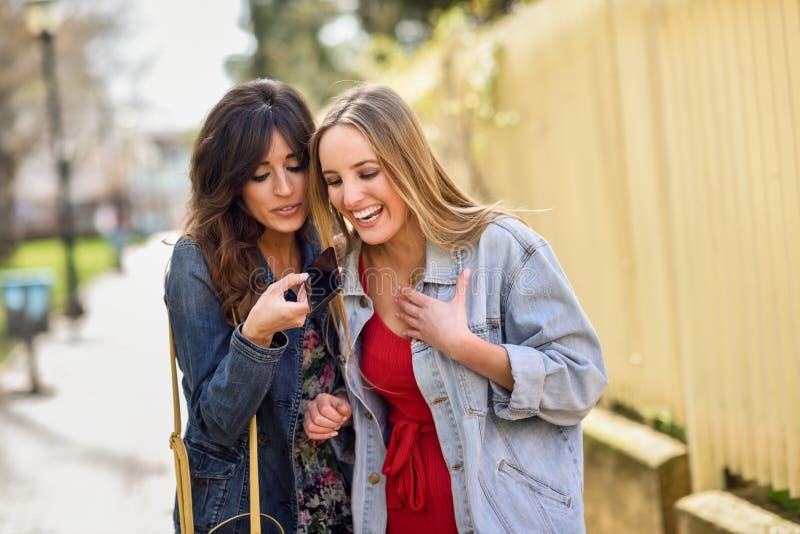 Δύο νέες γυναίκες που χρησιμοποιούν την αναγνώριση φωνής του τηλεφώνου υπαίθριου στοκ εικόνες με δικαίωμα ελεύθερης χρήσης