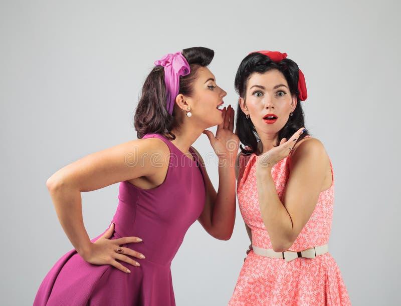 Δύο νέες γυναίκες που ψιθυρίζουν το κουτσομπολιό στοκ εικόνες με δικαίωμα ελεύθερης χρήσης