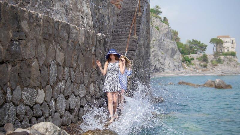 Δύο νέες γυναίκες στα panamas που περπατούν κάτω στην προκυμαία στοκ εικόνες με δικαίωμα ελεύθερης χρήσης