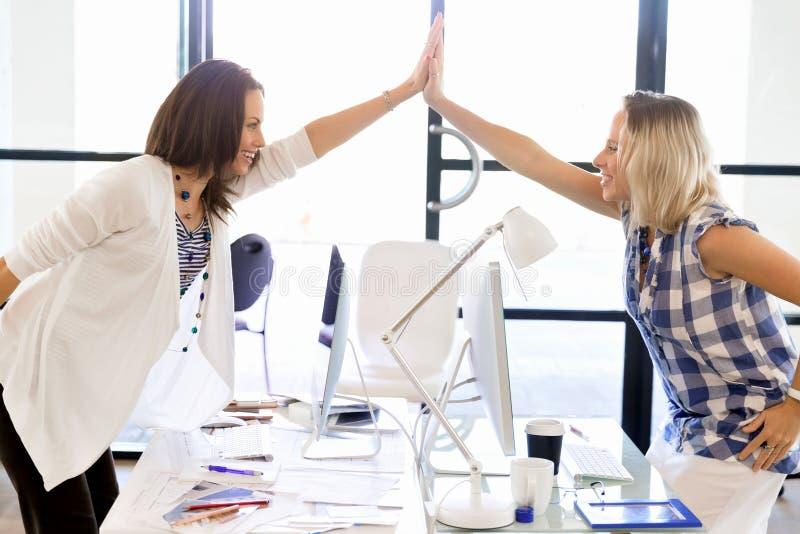 Δύο νέες γυναίκες στην επιτυχία εορτασμού γραφείων στοκ φωτογραφία