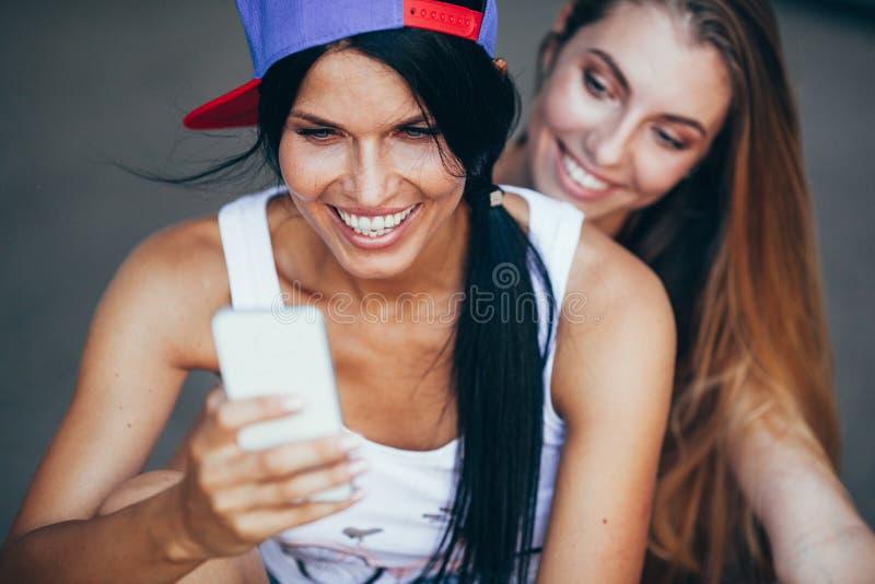 Δύο νέες ενήλικες γυναίκες με το lonboard στοκ εικόνα