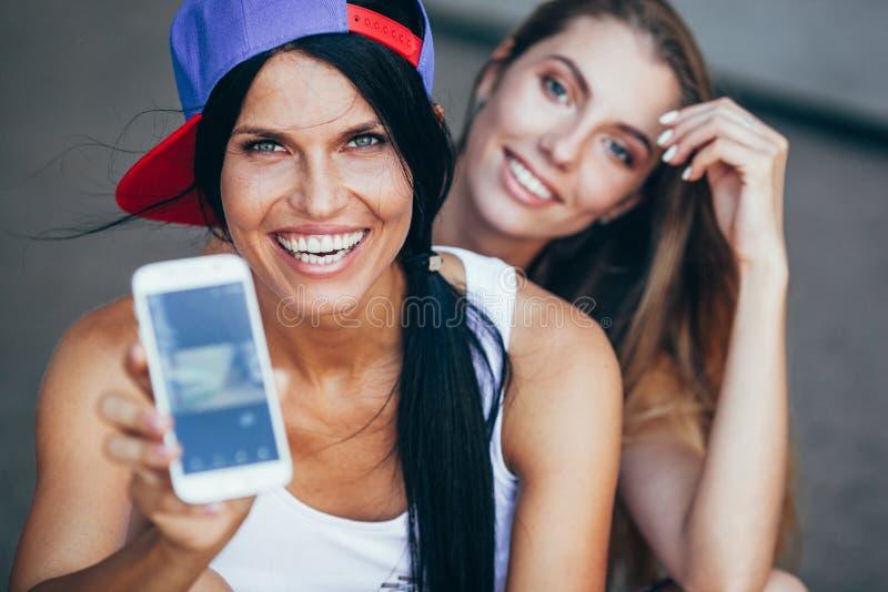 Δύο νέες ενήλικες γυναίκες με το smartphone στοκ φωτογραφίες