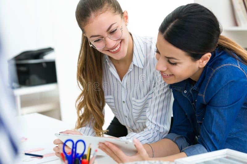 Δύο νέες επιχειρηματίες που χρησιμοποιούν αυτοί ψηφιακή ταμπλέτα στο ράβοντας εργαστήριο στοκ εικόνα