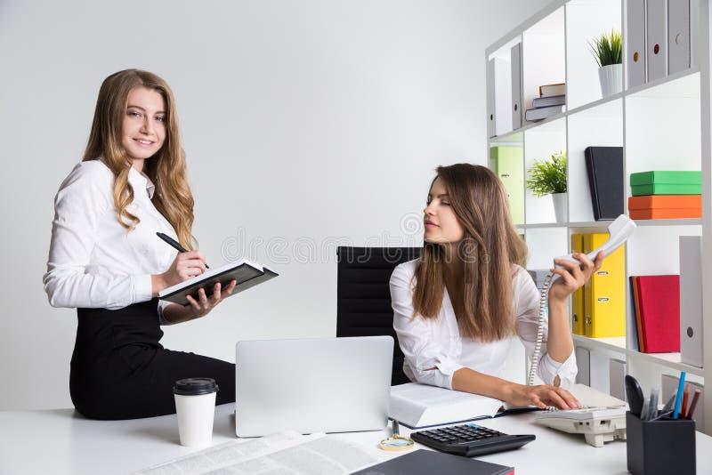 Δύο νέες επιχειρησιακές κυρίες στον εργασιακό χώρο στο άσπρο γραφείο στοκ εικόνα με δικαίωμα ελεύθερης χρήσης
