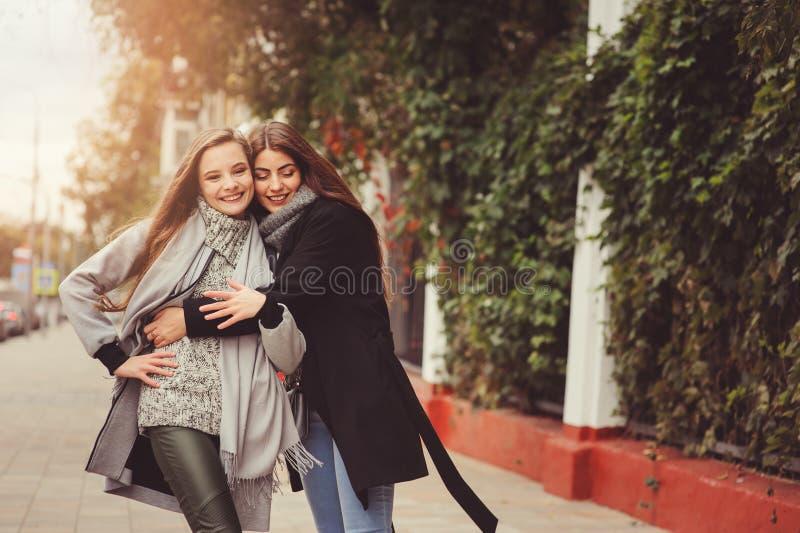 Δύο νέες ευτυχείς φίλες που περπατούν στις οδούς πόλεων στις περιστασιακές εξαρτήσεις μόδας στοκ εικόνα με δικαίωμα ελεύθερης χρήσης