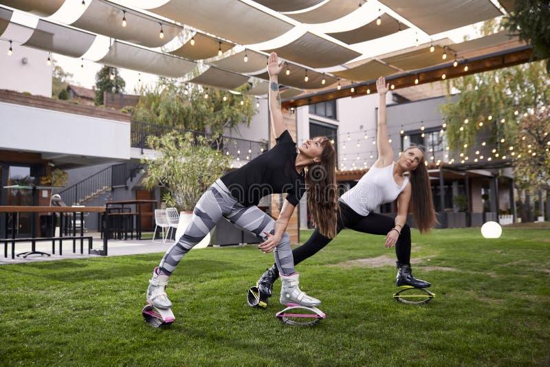 Δύο νέες κυρίες, 20-29 χρονών, που κάνουν κάποιο είδος άσκησης στις μπότες άλματος, στοκ εικόνες