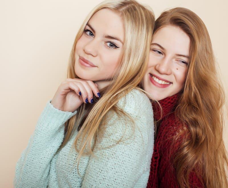 Δύο νέες φίλες στα χειμερινά πουλόβερ στο εσωτερικό που έχουν τη διασκέδαση lifestyle Οι ξανθοί φίλοι εφήβων κλείνουν επάνω στοκ φωτογραφία