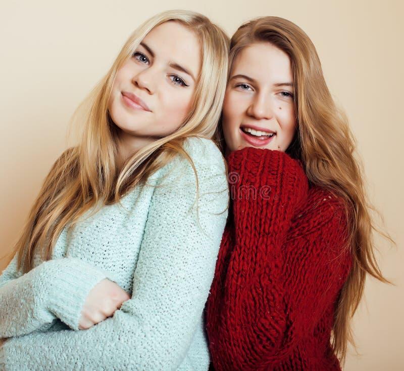 Δύο νέες φίλες στα χειμερινά πουλόβερ στο εσωτερικό που έχουν τη διασκέδαση lifestyle Οι ξανθοί φίλοι εφήβων κλείνουν επάνω στοκ εικόνα