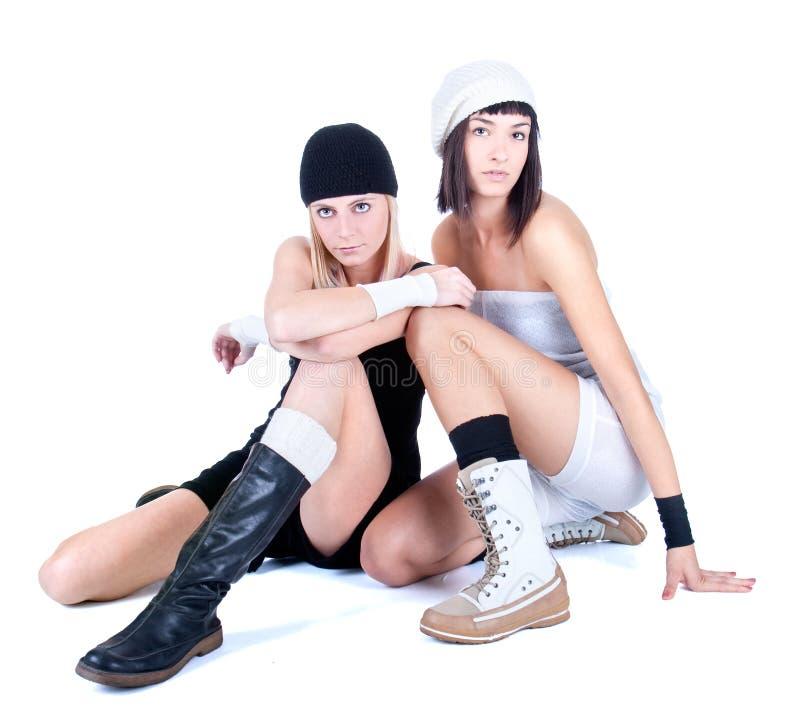 Δύο νέες όμορφες γυναίκες που κάθονται και που θέτουν στοκ φωτογραφία με δικαίωμα ελεύθερης χρήσης