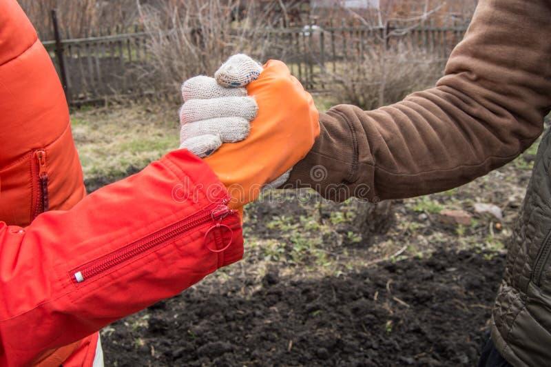 Δύο νέοι αγρότες τινάζουν τα χέρια στο υπόβαθρο του χώματος την άνοιξη, η συμφωνία του αγρότη Η έννοια της ομαδικής εργασίας μέσα στοκ εικόνες
