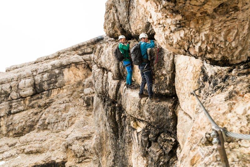 Δύο νέοι ελκυστικοί αρσενικοί ορειβάτες βουνών πολύ εκθεμένος μέσω Ferrata στους δολομίτες της Ιταλίας στοκ εικόνες με δικαίωμα ελεύθερης χρήσης