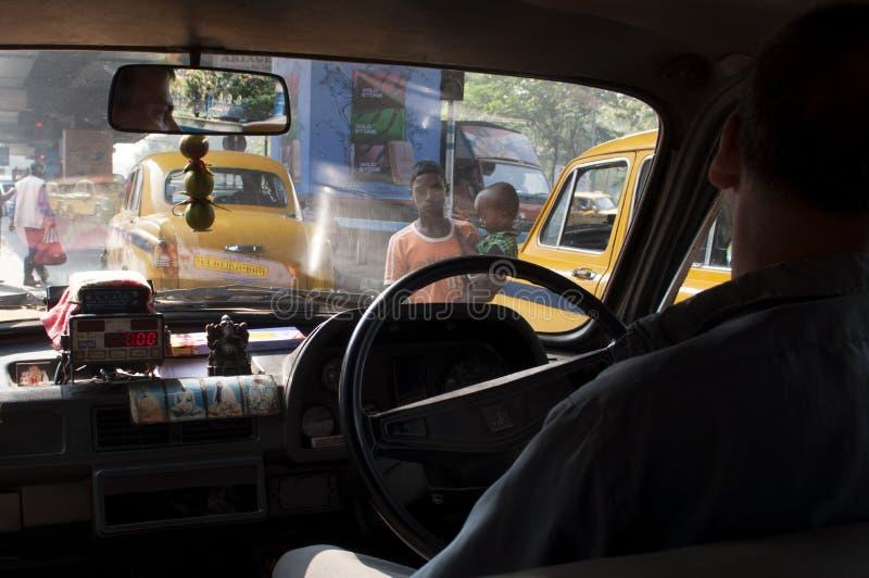 Δύο νέοι επαίτες, το μωρό με acrocephaly, περίπατος στην κυκλοφορία σε Kolkata στοκ εικόνα