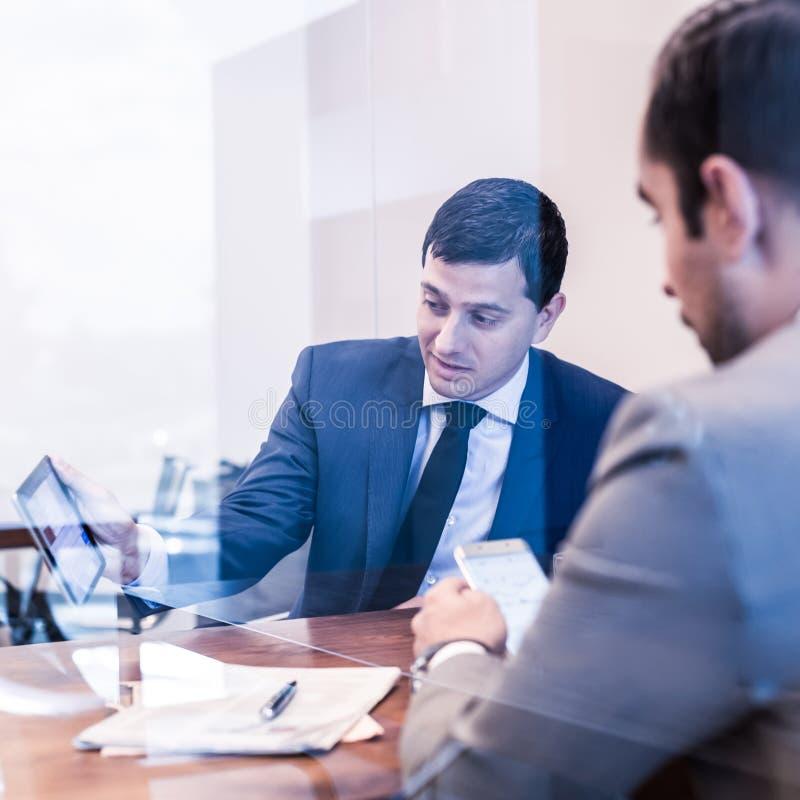Δύο νέοι επιχειρηματίες που χρησιμοποιούν τις ηλεκτρονικές συσκευές στην επιχειρησιακή συνεδρίαση στοκ εικόνες