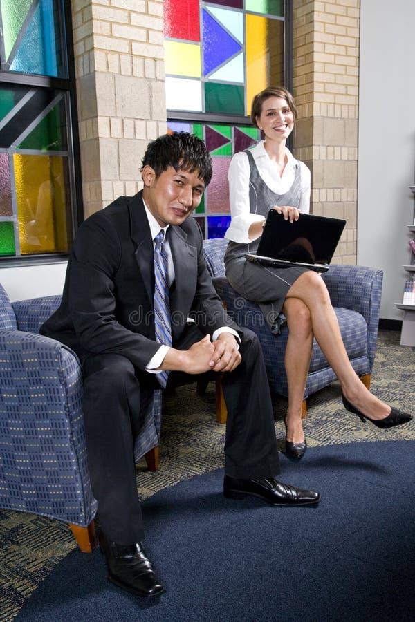 Δύο νέοι επιχειρησιακοί εργαζόμενοι στη αίθουσα αναμονής γραφείων στοκ εικόνες με δικαίωμα ελεύθερης χρήσης