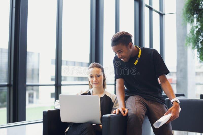 Δύο νέοι σπουδαστές που χρησιμοποιούν το lap-top στην πανεπιστημιούπολη στοκ φωτογραφίες