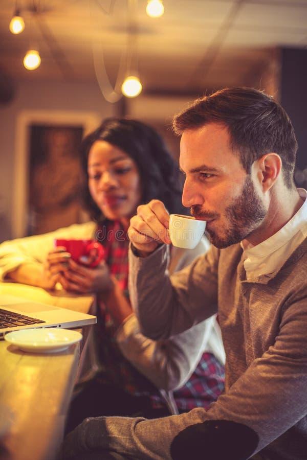 Δύο νέοι συνάδελφοι στον καφέ που λειτουργεί στο lap-top στοκ εικόνα με δικαίωμα ελεύθερης χρήσης