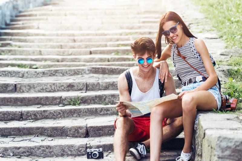 Δύο νέοι τουρίστες που χαλαρώνουν και που εξετάζουν έναν χάρτη οδηγών στοκ εικόνες