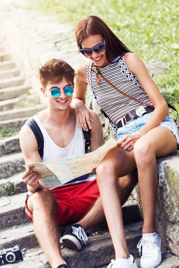 Δύο νέοι τουρίστες που χαλαρώνουν και που εξετάζουν έναν χάρτη οδηγών στοκ εικόνα