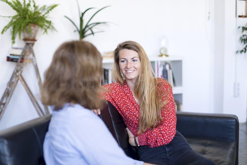 Δύο νέοι φίλοι σε έναν καναπέ στο καθιστικό στο σπίτι στοκ εικόνες
