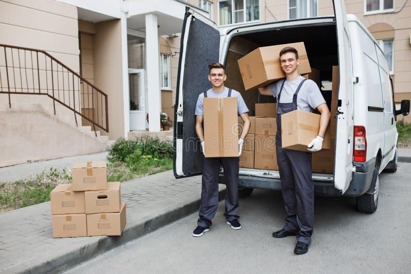 Δύο νέοι όμορφοι χαμογελώντας εργαζόμενοι που φορούν τις στολές στέκονται μπροστά από το σύνολο φορτηγών των κιβωτίων που κρατά τ στοκ εικόνες με δικαίωμα ελεύθερης χρήσης