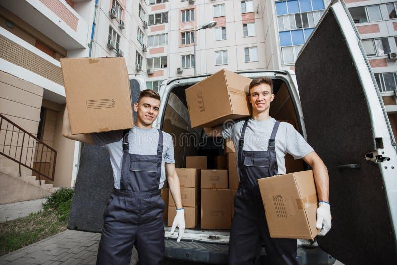 Δύο νέοι όμορφοι χαμογελώντας εργαζόμενοι που φορούν τις στολές στέκονται μπροστά από το σύνολο φορτηγών των κιβωτίων που κρατά τ στοκ φωτογραφία με δικαίωμα ελεύθερης χρήσης