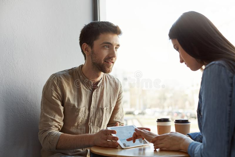 Δύο νέοι pesrpective επιχειρηματίες στον καφέ κατανάλωσης συνεδρίασης, ομιλία για το μελλοντικό πρόγραμμα ξεκινήματος και κοίταγμ στοκ εικόνες