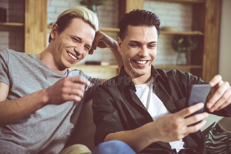 Δύο νεαροί άνδρες που εξετάζουν την οθόνη και το γέλιο smartphone στοκ εικόνα