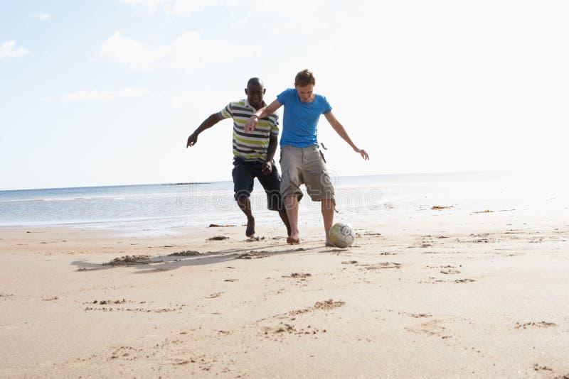 Δύο νεαροί άνδρες που παίζουν το ποδόσφαιρο στην παραλία από κοινού στοκ εικόνα