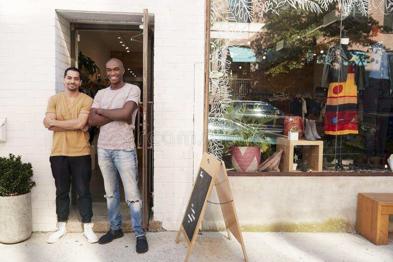 Δύο νεαροί άνδρες που χαμογελούν στη κάμερα έξω από το κατάστημα ενδυμάτων τους στοκ φωτογραφίες