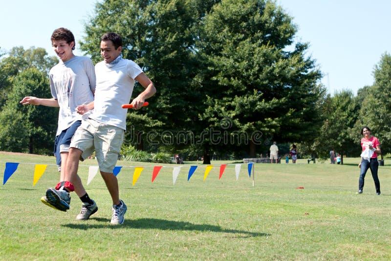 Δύο νεαροί άνδρες ανταγωνίζονται στην τρίποδος φυλή στο θερινό έρανο στοκ εικόνες με δικαίωμα ελεύθερης χρήσης