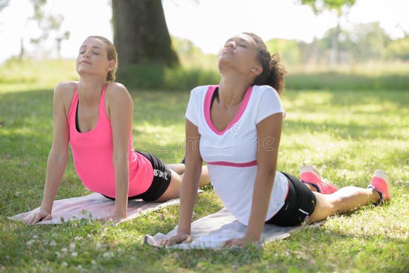 Δύο νεολαίες εγκαθιστούν τις γυναίκες που κάνουν pilates την ανύψωση άσκησης upperbody υπαίθρια στοκ φωτογραφίες με δικαίωμα ελεύθερης χρήσης