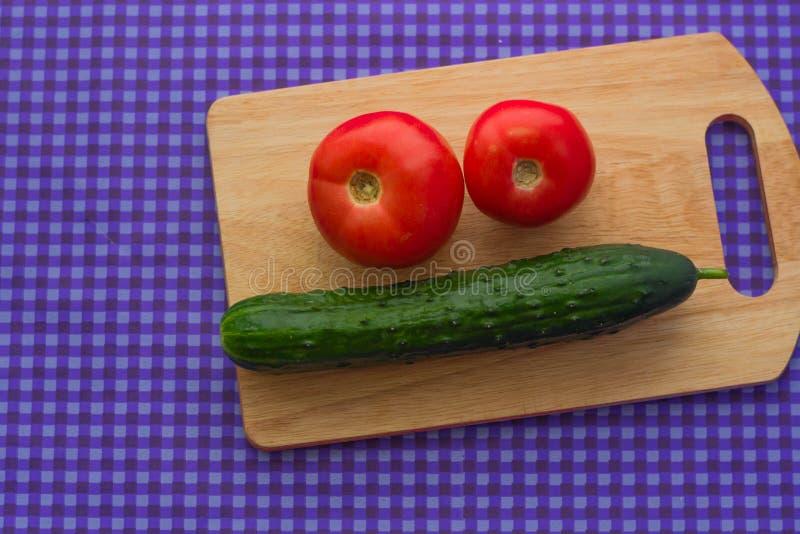 Δύο ντομάτες και ένα αγγούρι σε έναν ξύλινο πίνακα σε ένα πορφυρό υπόβαθρο στοκ φωτογραφία με δικαίωμα ελεύθερης χρήσης